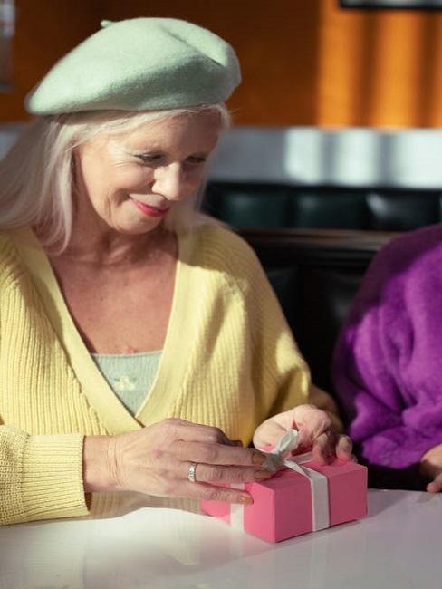 Kobieta rozpakowująca prezent na 70 urodziny