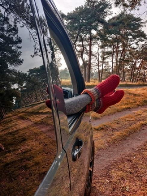 Osoba wystawiająca nogi z okna samochodu