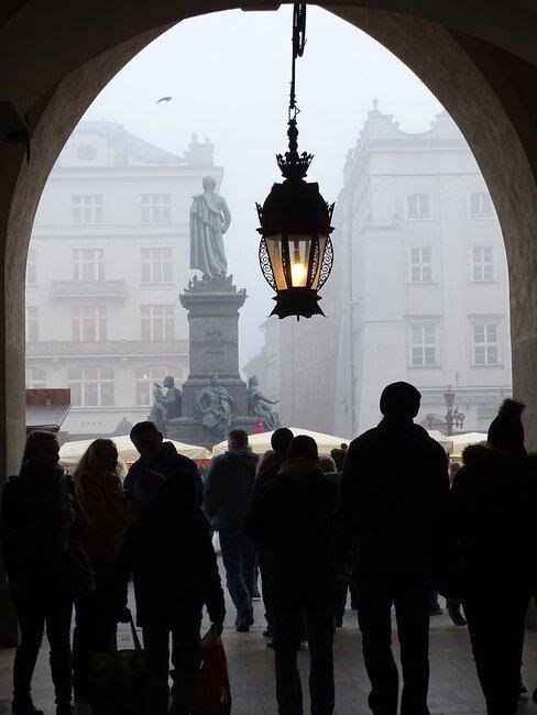 Ludzie ukryci przed deszczem patrzą na pomnik Mickiewicza