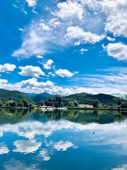 Widok nad jezioro pod błękitnym niebem z chmurami
