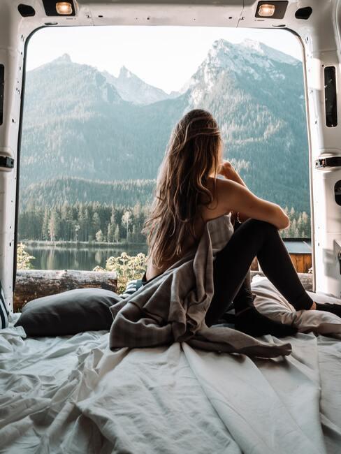 Kobieta patrząca z okna kampera na jezioro