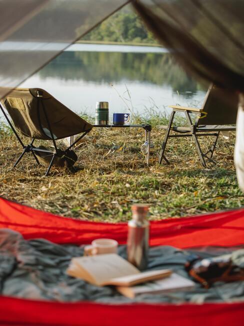widok z namiotu na dwa rozkładane krzesła nad jeziorem