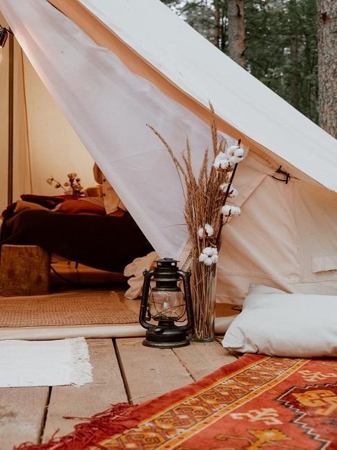 Wnętrze eleganckiego namiotu, kwiaty i poduszki obok