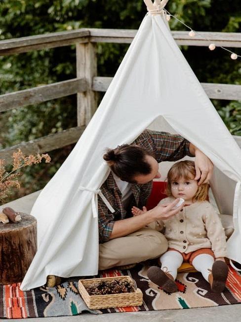 Ojciec i dziecko siedzą przed namiotem