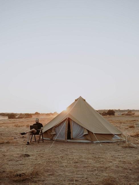 Mężczyzna siedzący obok namiotu