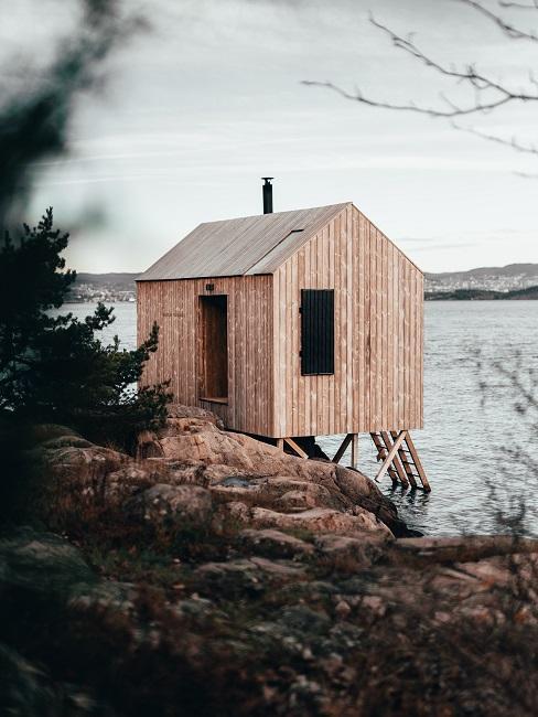 Drewniany tiny house na tle jeziora