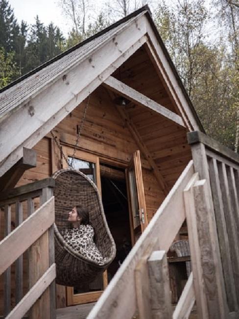 Kobieta siedząca na wiszącym fotelu na tarasie małego domu
