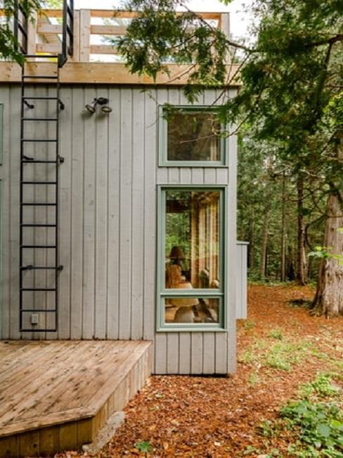 Tiny house z drabinką na ścianie w lesie
