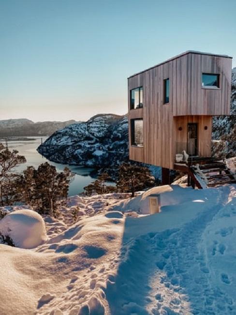 Tiny house zimą na tle gór i jeziora