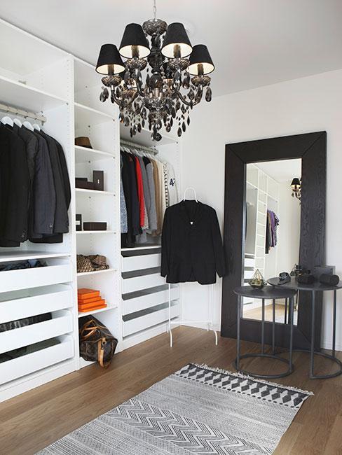 duża biała otwata garderona w białoczarnej sypialni z czarnym lustrem podłogowym i czarnym barokowym żyrandolem
