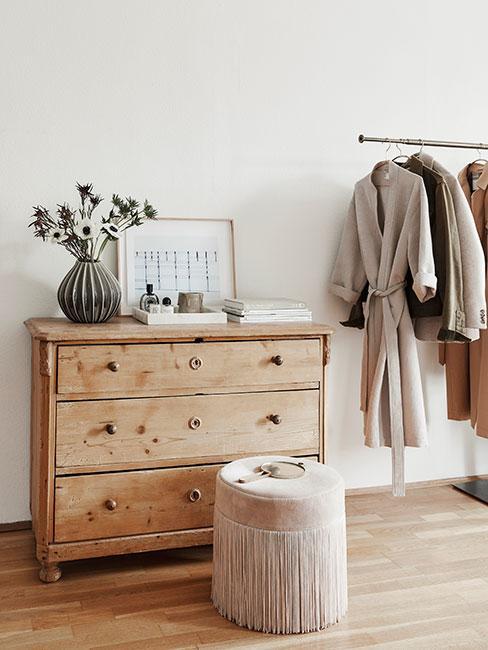 Drewniana komoda oraz drążek z ubraniami