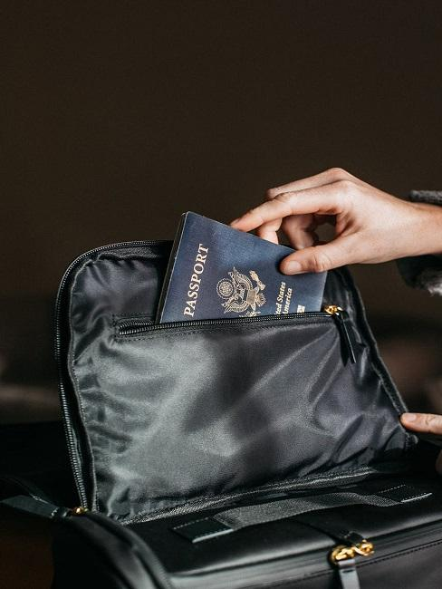 Ręka wkładająca paszport do torby