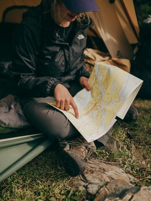Kobieta czyta mapę siedząc pod namiotem