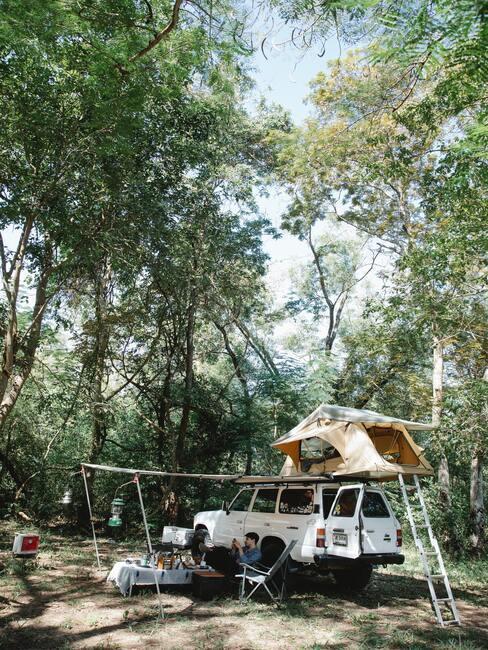 Samochód z namiotem na dachu, para odpoczywająca obok