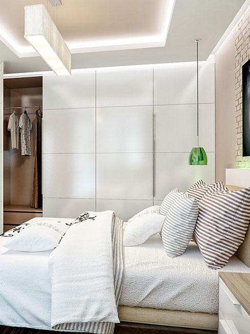 mała garderoba zabudowana w jasnej sypialni