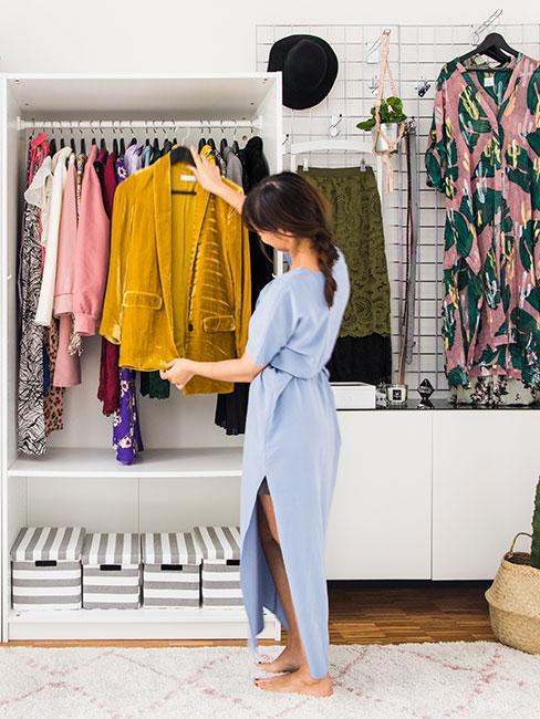 kobieta stojąca przed małą garderobą z letnimi strojami