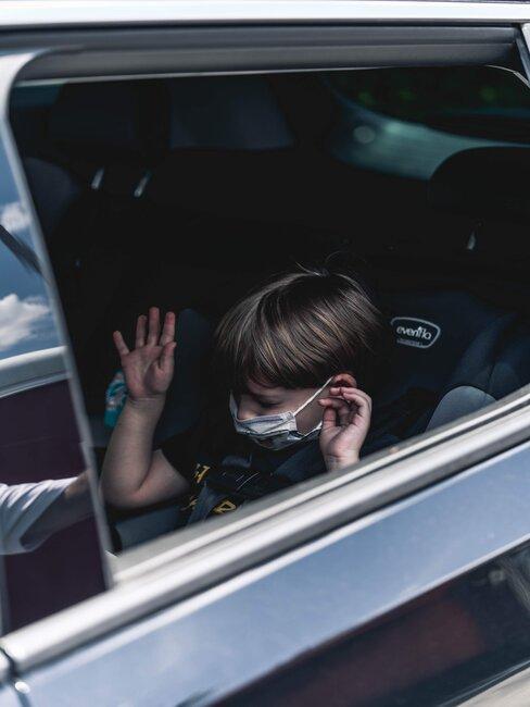 Dziecko na tylnym siedzeniu samochodu, w foteliku i masce