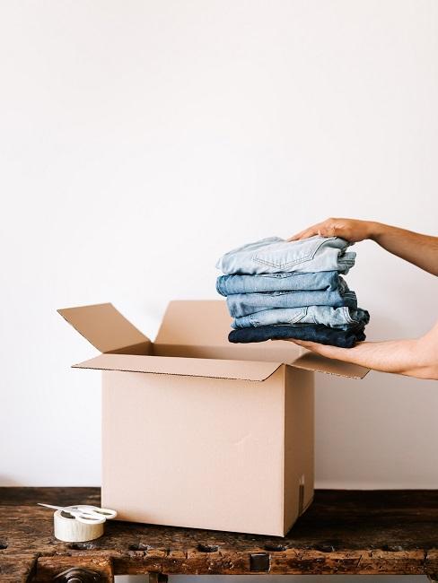 Dłonie pakujące spodnie do kartonu