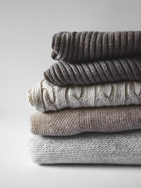 Złożone swetry na białym tle
