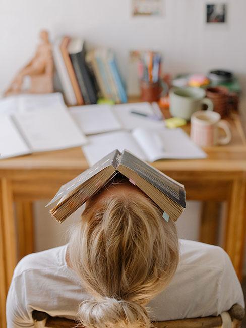 nastolatka śpiąca przy biurku z książką na głowie