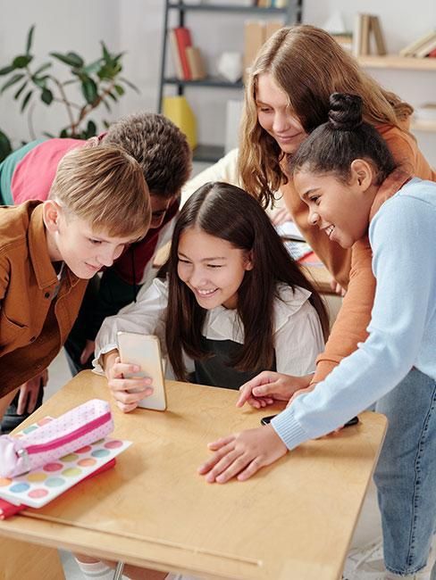 grupa dzieci wczesnoszkolnych oglądająca filmik na telefonie