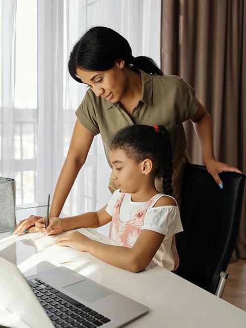 córka odrabiająca lekcje przy komputerze z mamą