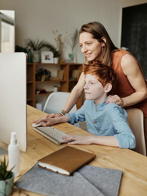synek odrabiający lekcje przy komputerze z mamą