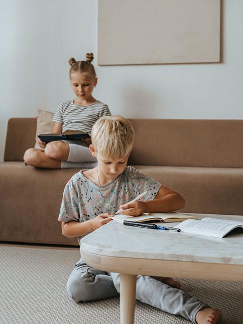 młodsze dzieci czytające w salonie