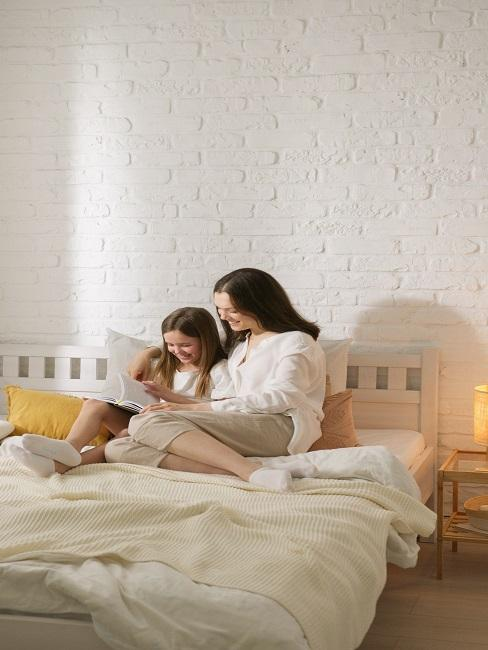 Matka z córką siedzące na łóżku i czytające najlepsze bajki