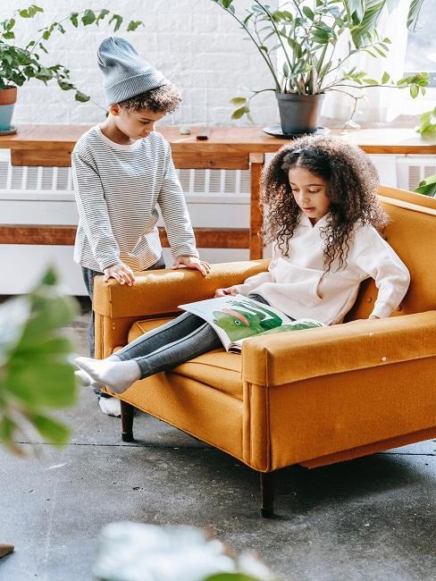 Dziewczynka siedząca na pomarańczowej kanapie i czytająca bajkę