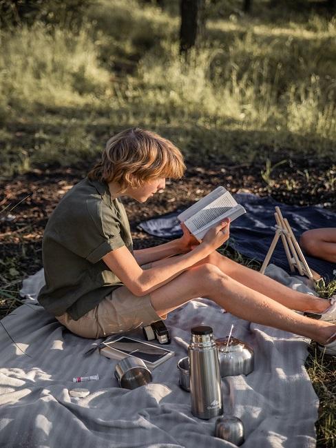 Chłopak czytający książkę na kocu
