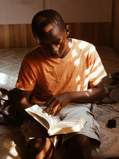 Chłopak w pomarańczowej koszulce czytający książkę
