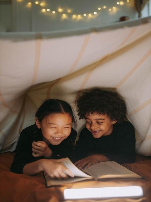 Chłopczyk z dziewczynką w namiocie czytają najlepsze bajki