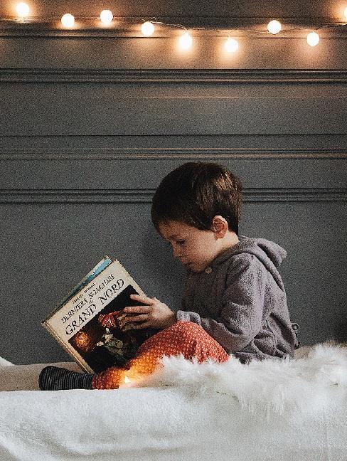 Chłopczyk siedzący na łóżku i czytający najlepsze bajki