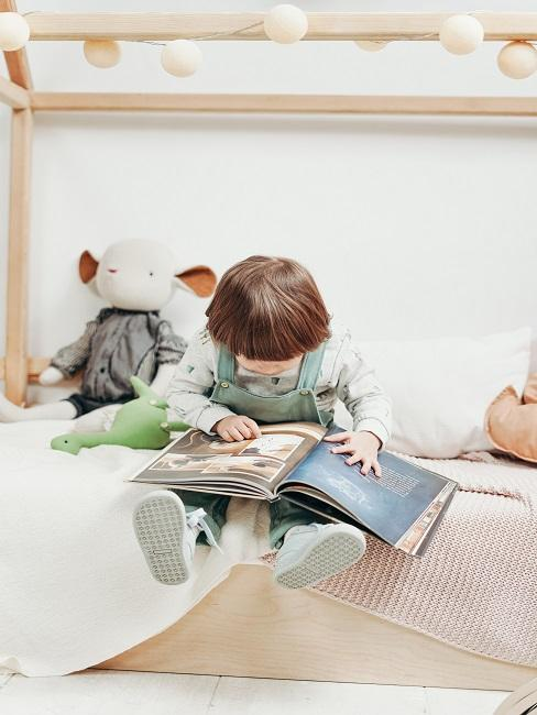 Chłopiec siedzący na łóżku i oglądający książkę