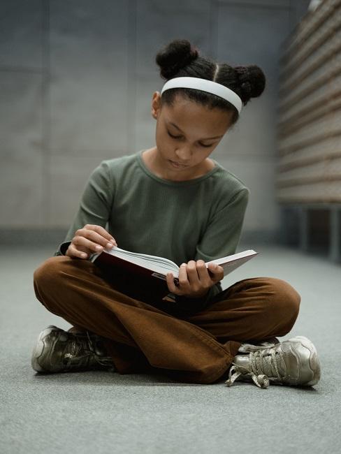 Dziewczynka siedząca na ziemi i czytająca najlepsze bajki