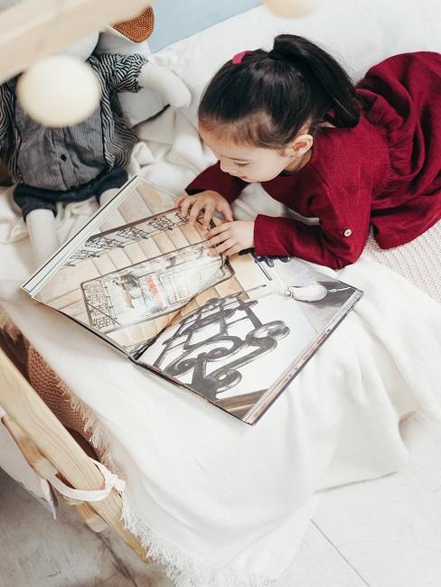 Dziewczynka leżąca na łóżku i przeglądająca książkę