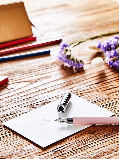 Biała kartka na stole na życzenia na ślub z różowym piórem