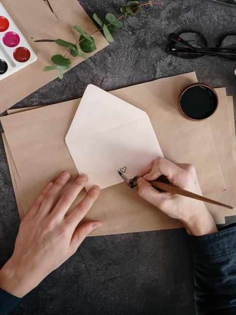 Dłonie tworzące kartkę na życzenia na ślub