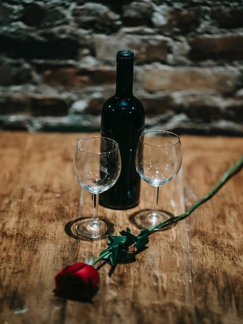 Wino i kieliszki na stole z różą na świętowanie 3 rocznicy ślubu