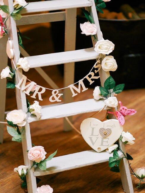"""Dekoracja weselna z kwiatami i napisem """"Mr & Mrs"""""""