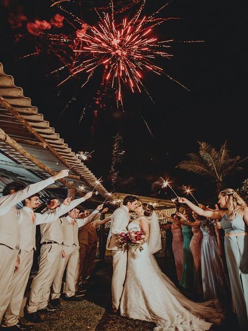Para młoda stoi w środku, a dookoła goście z zimnymi ogniami jako atrakcja na wesele