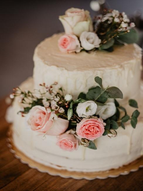 Biały tort weselny z ozdobnymi kwiatami jako atrakcja na wesele