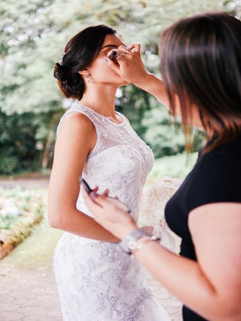 Makijażysta maluje pannę młodą - warsztaty makijażowe jako atrakcja na wesele