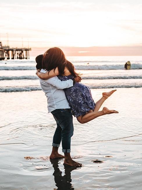 Ciesząca się para z zaręczyn na tle plaży