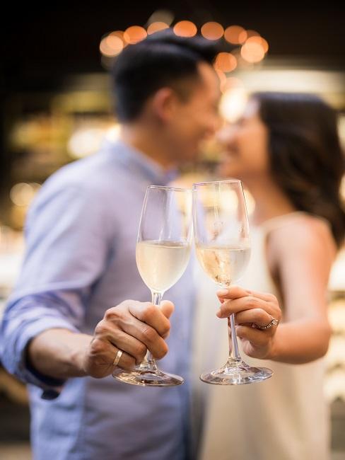 Uśmiechająca się para trzymająca kieliszki z szampanem - zaręczyny w restauracji
