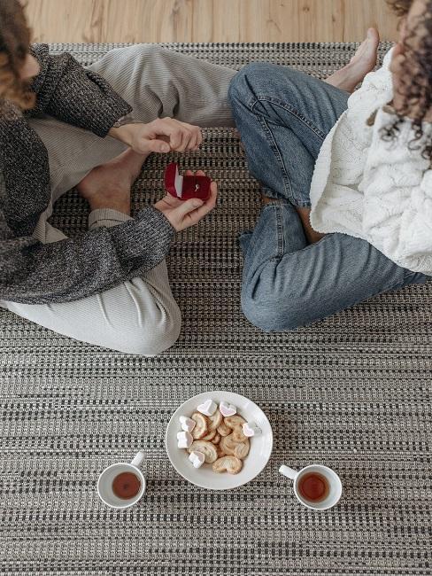Para siedząca za ziemi z herbatą i słodkościami