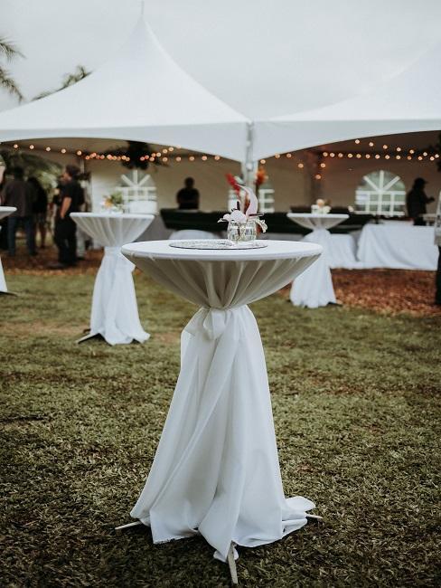 Wysokie stołki oraz namiot w tle na ślub w plenerze