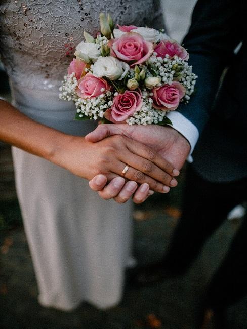 Dłonie Pary Młodej z bukietem kwiatów