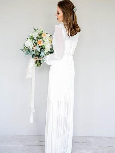 Panna Młoda w białej, długiej sukni z bukietem na białym tle
